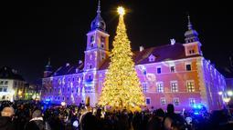 Orang-orang mengabadikan foto pohon Natal yang diterangi lampu di Castle Square di Warsawa, Polandia, pada 5 Desember 2020. Dinyalakannya lampu pohon Natal besar di Castle Square di Warsawa pada Sabtu (5/12) menandai pembukaan resmi musim Natal di Polandia. (Xinhua/Jaap Arriens)