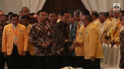 Presiden Joko Widodo (Jokowi) menyalami menyalami Ketua Dewan Pembina Golkar Aburizal Bakrie saat menghadiri pembukaan Munaslub Partai Golkar di Jakarta, Senin (18/12). Munaslub Golkar berlangsung hingga 20 Desember 2017. (Liputan6.com/Angga Yuniar)