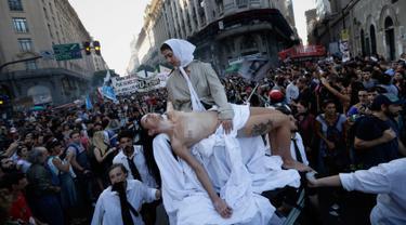Seorang wanita bertelanjang dada saat menggelar aksi teatrikal yang melambangkan ibu Plaza de Mayo saat pawai parade peringatan 41 tahun kudeta militer di Buenos Aires, Argentina (24/3). (AP Photo/Victor R. Caivano)