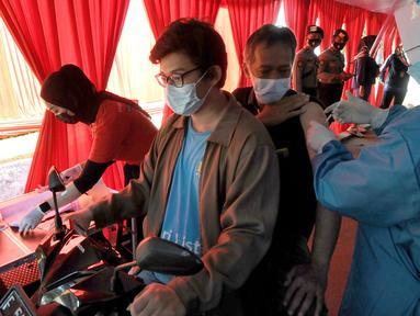 Paramedis menyuntikkan vaksin COVID-19 secara drive thru kepada penumpang sepeda motor di GOR Pajajaran, Kota Bogor, Jawa Barat, Rabu (17/3/2021). Kegiatan ini diselenggarakan oleh Halodoc, Gojek, dan Pemkot Bogor. (merdeka.com/Arie Basuki)