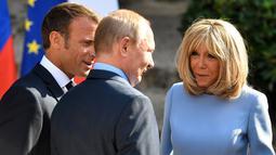 Presiden Prancis Emmanuel Macron (kiri) dan istrinya Brigitte Macron (kanan) menyambut Presiden Rusia Vladimir Putin (tengah) di Benteng Bregancon, Bormes-les-Mimosas, Prancis, Senin (19/8/2019). Macron dan Putin mencoba meningkatkan hubungan Uni Eropa dengan Moskow. (Gerard JULIEN/POOL/AFP)