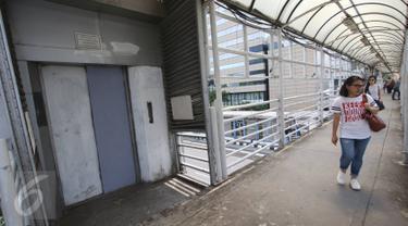 Warga melintas di depan lift khusus lansia dan ibu hamil yang rusak di JPO Sarinah, Jakarta, Kamis (2/3). Kurangnya perhatian pihak terkait menyebabkan lift tersebut menjadi terbengkalai serta tidak berguna. (Liputan6.com/Immanuel Antonius)