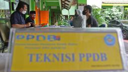 ng tua murid mencari informasi pengajuan akun untuk mengikuti proses PPDB 2021/2022 di SMA Negeri 87 Jakarta, Senin (7/6/2021). Pada tahun ini, ada empat jalur pendaftaran yang dibuka meliputi jalur prestasi, afirmasi, zonasi, perpindahan tugas orang tua dan anak guru. (Liputan6.com/Herman Zakharia)
