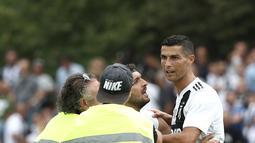 Seorang suporter berusaha memeluk penyerang Juventus, Cristiano Ronaldo selama pertandingan persahabatan antara Juventus A dan tim B, di Villar Perosa, Italia utara, (12/8). Pada pertandingan ini Ronaldo mencetak satu gol. (AFP Photo/Isabella Bonotto)