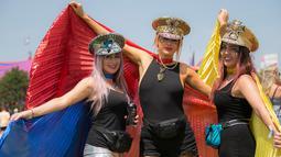 Tiga wanita berkostum unik berpose saat hari ketiga Festival Glastonbury di Worthy Farm, Somerset, Inggris (28/6/2019). Gelombang panas yang melanada bagian-bagian Eropa tidak menyurutkan pengunjung untuk berkumpul di festival ini. (AP Photo/Joel C Ryan)