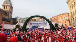 Peserta mengenakan kostum Sinterklas ikut serta dalam kegiatan amal Santa's Fun Run di Riga, Latvia, Minggu (8/12/2019). Ini merupakan acara amal yang pesertanya bersenang-senang dengan berlari atau berjalan kaki untuk mengumpulkan dana bagi anak-anak di rumah sakit Latvia. (Gints Ivuskans/AFP)