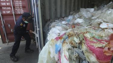 Petugas membuka peti kemas berisi sampah plastik yang mengandung limbah berbahaya dan beracun (B3) untuk di re-ekspor di Batam, Senin (29/7/2019). Indonesia mengirim kembali (re-ekspor) tujuh peti kemas berisi limbah plastik impor ke negara asalnya, Prancis dan Hongkong. (SEI RATIFA/AFP)