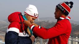 Atlet kereta luncur wanita AS Lauren Gibbs mengalungi medali perak kepada putri Presiden AS, Ivanka Trump selama kejuaraan Olimpiade Musim Dingin Pyeongchang 2018 di depan menara lompat ski di Pyeongchang (25/2). (AFP Photo/Pool/Eric Gaillard)