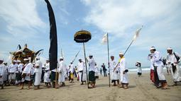 Umat Hindu menyusuri pantai saat menggelar ritual Melasti di Pantai Petitenget, Denpasar, Bali, Senin (4/3). Dalam sejarah, Melasti disimbolkan dengan gunungan sesaji yang dihanyutkan ke laut. (SONNY TUMBELAKA/AFP)
