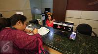 Teller berpakaian daerah melayani nasabah yang melakukan transaksi di Kantor Cabang Khusus (KCK) BRI, Jakarta, Jumat (21/4). Memperingati Hari Kartini, seluruh pegawai BRI mengenakan pakaian daerah dalam melayani nasabahnya. (Liputan6.com/Faizal Fanani)