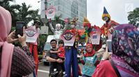 Warga foto bersama badut yang tengah menyosialisasikan sistem tilang Electronic Traffic Law Enforcement (ETLE) kepada pengunjung car free day (CFD) di Bundaran HI, Jakarta, Minggu (25/11). (Merdeka.com/Iqbal Nugroho)