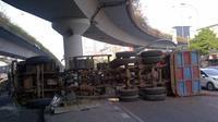 Sebuah truk terguling dan melintang di badan jalan di bawah jembatan layang Matraman, Jakarta Timur.