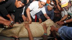 Keluarga dan sahabat saat akan memasukkan jenazah Mpok Nori ke dalam liang lahat di TPU Pondok Ranggon, Jakarta Timur, Jumat (3/4/2015). (Liputan6.com/Helmi Afandi)