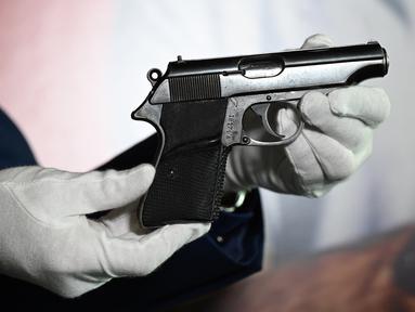 """Pistol PP Walther yang digunakan Sean Connery dalam film James Bond pertama, """"Dr. No"""" (1962) saat pratinjau pers di Beverly Hills, California, Selasa (23/11/2020). Properti film itu diperkirakan terjual sekitar Rp2,1 miliar hingga Rp2,8 miliar di Julien's Auctions pada 3 Desember. (Robyn Beck/AFP)"""