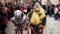 Peserta mengenakan kostum Charlie Chaplin (kanan) saat mengikuti karnaval di desa Vevcani, Macedonia (13/1). Karnaval Vevcani ini diadakan setiap tahun pada malam pesta Santo Basil. (AFP Photo/Robert Atanasovski)