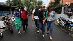 Polisi mengawal tersangka usai menggerebek peredaran narkoba di kawasan Kampung Ambon, Cengkareng, Jakarta Barat, Rabu (24/1). Seorang tersangka berhasil kabur melalui lubang pintu belakang. (Liputan6.com/Arya Manggala)