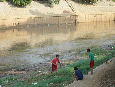Anak-anak bermain di bantaran Sungai Ciliwung yang mengering, kawasan Kampung Melayu, Jakarta, Jumat (8/11/2019). Curah hujan yang tidak menentu menyebabkan sebagian bantaran Ciliwung masih mengalami kekeringan. (Liputan6.com/Immanuel Antonius)