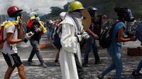 Demonstran anti- Nicolas Maduro memegang botol tinja untuk dilemparkan ke polisi anti huru-hara di Caracas, Venezuela, 10 Mei 2017. Mereka kini menggunakan bom 'poopootov' untuk menyerang petugas yang menghalangi jalannya demo. (AP Photo/Ariana Cubillos)