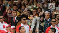 Presiden Joko Widodo saat menyalakan api obor Asian Games 2018 sebelum upacara penurunan Bendera Merah Putih di Istana Negara Jakarta, Jumat (17/8). (Liputan6.com/Pool/Eko)