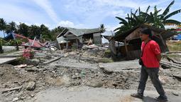 Seorang pria berjalan melewati jalan rusak usai gempa dan tsunami melanda Kabupaten Sigi, Sulawesi Tengah, Kamis (4/10). BNPB mengatakan ada empat kecamatan sulit dijangkau petugas usai gempa dan tsunami melanda daerah tersebut. (ADEK BERRY/AFP)