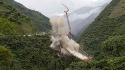 Peruntuhan sebuah jembatan gantung oleh para insinyur di Chirajara, Kolombia, Rabu (11/7). Sebelumnya, sebagian jembatan runtuh dan menewaskan sembilan pekerja saat pembangunannya pada Januari lalu. (AP Photo/Fernando Vergara)