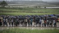 Pengungsi Muslim Rohingya menunggu antrean distribusi makanan saat hujan di kamp pengungsi Nayapara, Bangladesh (6/10). Bangladesh akan membangun kamp pengungsi terbesar di dunia untuk menampung 800.000 orang. (AFP PHOTO/Fred Dufour)