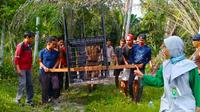 Personel BBKSDA Riau dan masyarakat Kota Dumai memasang perangkap dari kerangkeng untuk menangkap beruang masuk pemukiman. (Liputan6.com/M Syukur)