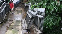 Pejalan kaki menaiki tangga JPO yang rusak di Terminal Kampung Rambutan, Jakarta, Senin (28/1). Kondisi JPO yang sebagian pagar pembatasnya rusak tersebut membahayakan pejalan kaki apabila tidak segera diperbaiki. (Liputan6.com/Immanuel Antonius)