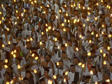 Umat muslim mengikuti pawai obor menyambut Tahun Baru Islam 1441 H pada acara Jakarta Muharram Festival di kawasan Bundaran HI, Jakarta, Sabtu (31/8/2019). Pawai yang diikuti 4000 peserta dimulai dari Jalan Merdeka Barat, Silang Monas, menuju Bundaran HI. (merdeka.com/Imam Bukhori)