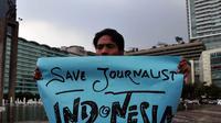 Seorang wartawan membentangkan poster saat aksi solidaritas tolak kekerasan terhadap jurnalis di Bundaran HI, Jakarta, Jumat (14/11/2014). (Liputan6.com/Johan Tallo)