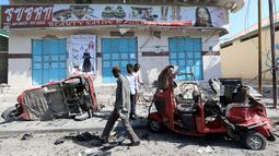 Sejumlah warga mengecek bajaj yang rusak parah usai terkena ledakan bom yang terjadi di Ibu Kota Mogadishu, Somalia (28/3). Hingga kini, belum ada pihak yang bertanggung jawab atas serangan ini. Namun, muncul dugaan kelompok militan berada di balik aksi tersebut. (Reuters/Feisal Omar)