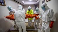 Tim penanganan membawa jenazah seorang pasien COVID-19 yang meninggal di rumah selama isolasi mandiri karena rumah sakit setempat tidak mampu lagi menampung pasien COVID-19 di Bogor, Jawa Barat, Senin (6/7/2021). (ADITYA AJI/AFP)