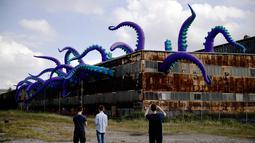 """Pengunjung mengambil gambar patung karet """"Sea Monsters HERE"""" di gudang berkarat Building 61 di Navy Yard, Philadelphia, Selasa (9/10). Kreasi sepanjang 40 kaki ini menampilkan tentakel ungu besar yang keluar dari jendela hingga ke atap. (AP/Matt Rourke)"""