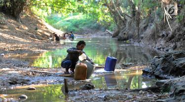 Warga mengambil air dari lubang pada aliran Sungai Cihoe untuk memenuhi kebutuhan sehari-hari termasuk air minum di kawasan Ridogalih, Cibarusah, Bekasi, Minggu (7/7/2019). Sudah lebih dari dua bulan, warga memanfaatkan sisa aliran sungai yang kotor akibat musim kemarau. (merdeka.com/Arie Basuki)