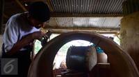 Seorang pengrajin menyelesaikan ukiran di atas kayu untuk dijadikan bedug di Desa Bleder, Ngasinan, Grabag, Magelang, Jawa Tengah, Jumat (3/6). Menjelang Ramadan, pengrajin bedug mulai kebanjiran order dari berbagai kota di Indonesia (Liputan6.com/Gholib)