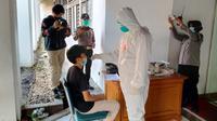 Pihak kepolisian menggelar tes swab antigen kepada massa yang melakukan unjuk rasa menolak perpanjangan PPKM darurat di halaman Gedung Sate, Kota Bandung, Rabu (21/7/2021). (Liputan6.com/Huyogo Simbolon)
