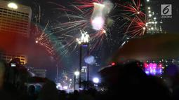 Kembang api menghiasi malam pergantian tahun baru 2019 di kawasan Bundaran HI, Jakarta, Selasa (1/1). Bundaran HI menjadi salah satu pilihan warga menikmati kembang api tahun baru. (Liputan6.com/Angga Yuniar)