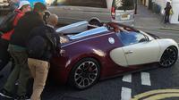 Pemilik Bugatti terpaksa turun dari mobil dan meminta kepada pemuda yang ada di sekitarnya untuk membantu mendorong mobil.