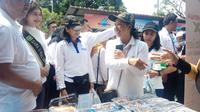 Menteri BUMN Rini Soemarno yang ikut berbelanja dan mencicipi jajanan di pasar murah yang diadakan oleh Pertamina untuk warga Lima Puluh, Pekanbaru.