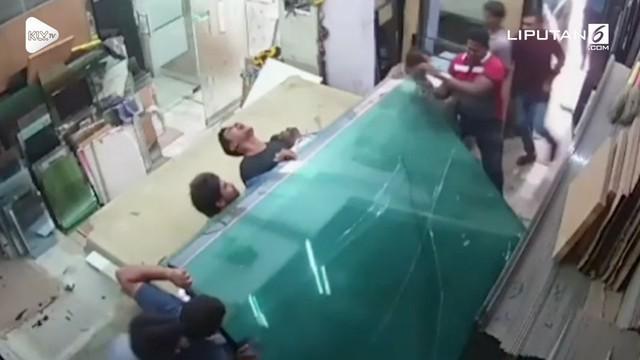 Sejumlah pekerja hilang keseimbangan saat mengangkut lembaran kaca. Akibatnya mereka tertimpa tumpukan kaca dan alami luka ringan.