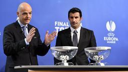 Sekretaris Jenderal UEFA Gianni Infantino (kiri) dan mantan bintang Real Madrid,   Luis Figo, mengambil bagian dalam undian untuk semifinal sepakbola Liga Champions di   markas UEFA di Nyon pada Jumat 11 April 2014 (AFP PHOTO/FABRICE COFFRINI)