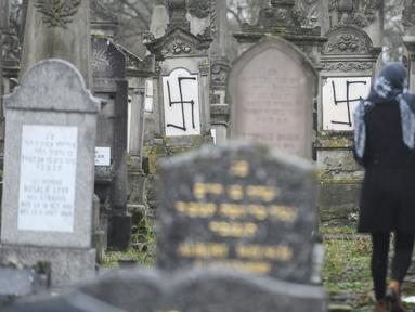Seorang wanita berjalan di sebuah pemakaman Yahudi di Strasbourg, Prancis (17/12). Sebanyak 37 batu nisan dirusak dengan lambang swastika Nazi yang dicat semprot dan grafiti lainnya. (AFP Photo/Sebastien Bozon)