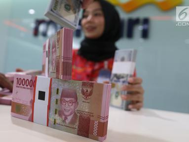 Teller tengah menghitung mata uang rupiah dan dolar di Bank Mandiri, Jakarta, Kamis (10/1). Nilai tukar rupiah terhadap dolar Amerika Serikat (AS) terus menguat di perdagangan pasar spot hari ini. Rupiah berada di zona hijau. (Liputan6.com/Angga Yuniar)