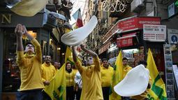 Anggota Pizzaioli Acrobats Coldiretti menunjukkan Pizzaioli untuk merayakan keputusan UNESCO di Naples, Italia, 7 Desember 2017. Pizzaioli adalah seni memutar adonan piza hingga mengembang dengan sempurna saat dipanggang. (Tiziana FABI/AFP)