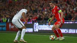 Gelandang Wales, Gareth Bale, berusaha melewati bek Azerbaijan, Pavlo Pashayev, pada laga Kualifikasi Piala Eropa 2020 di Cardiff City Stadium, Cardiff, Jumat (6/9). Wales menang 2-1 atas Azerbaijan. (AFP/Geoff Caddick)