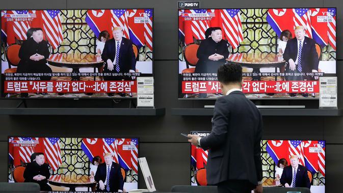 Seorang pria berdiri di dekat layar TV yang memperlihatkan siaran pertemuan antara Presiden AS Donald Trump dan pemimpin Korea Utara Kim Jong Un di Vietnam, di sebuah toko elektronik di Seoul, Korea Selatan (28/2). (AP Photo/Lee Jin-man)