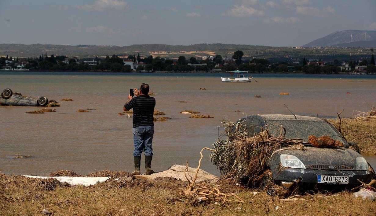 Penduduk lokal Christos Pavlou mengambil gambar mobilnya yang tenggelam setelah badai di desa Bourtzi di pulau Evia, Yunani, Senin (10/8/2020). Tujuh orang, termasuk dua lansia dan bayi berusia delapan bulan, tewas saat badai melanda pulau Evia pada Minggu kemarin. (AP Photo/Thanassis Stavrakis)