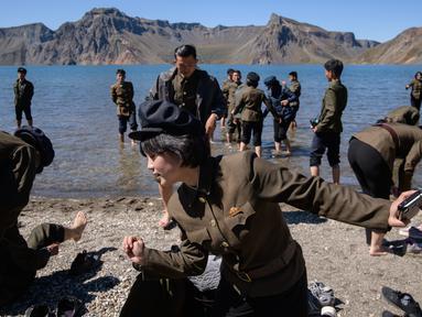 Gambar pada 11 September 2019 memperlihatkan siswa Korea Utara bermain di danau Chonji atau 'Heaven lake' saat mengunjungi kawasan Gunung Paektu di Samjiyon. 'Heaven lake' atau Danau surga ini ada di ketinggian 2.190 mdpl dan punya kedalaman 384 meter. (Photo by Ed JONES / AFP)