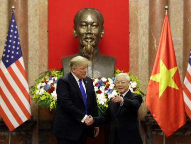 Presiden AS, Donald Trump bersalaman dengan Presiden Vietnam Nguyen Phu Trong di Istana Kepresidenan di Hanoi (27/2). Kunjungan Trump ke Vietnam untuk melakukan pertemuan tingkat tinggi dengan Pemimpin Korut, Kim Jong-un. (AP Photo/Evan Vucci)