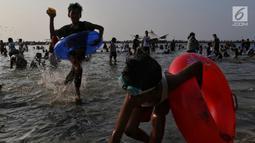 Pengunjung bermain dan berenang di kawasan Beach Pool, Taman Impian Jaya Ancol, Jakarta, Kamis (6/6/2019). Hari kedua Lebaran banyak dimanfaatkan warga untuk berlibur dan berekreasi bersama keluarga atau kerabat dengan mengunjungi pantai Ancol. (Liputan6.com/Johan Tallo)